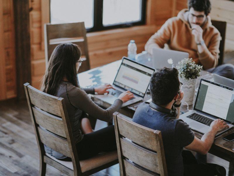 Žmonių grupė dirba prie nešiojamų kompiuterių